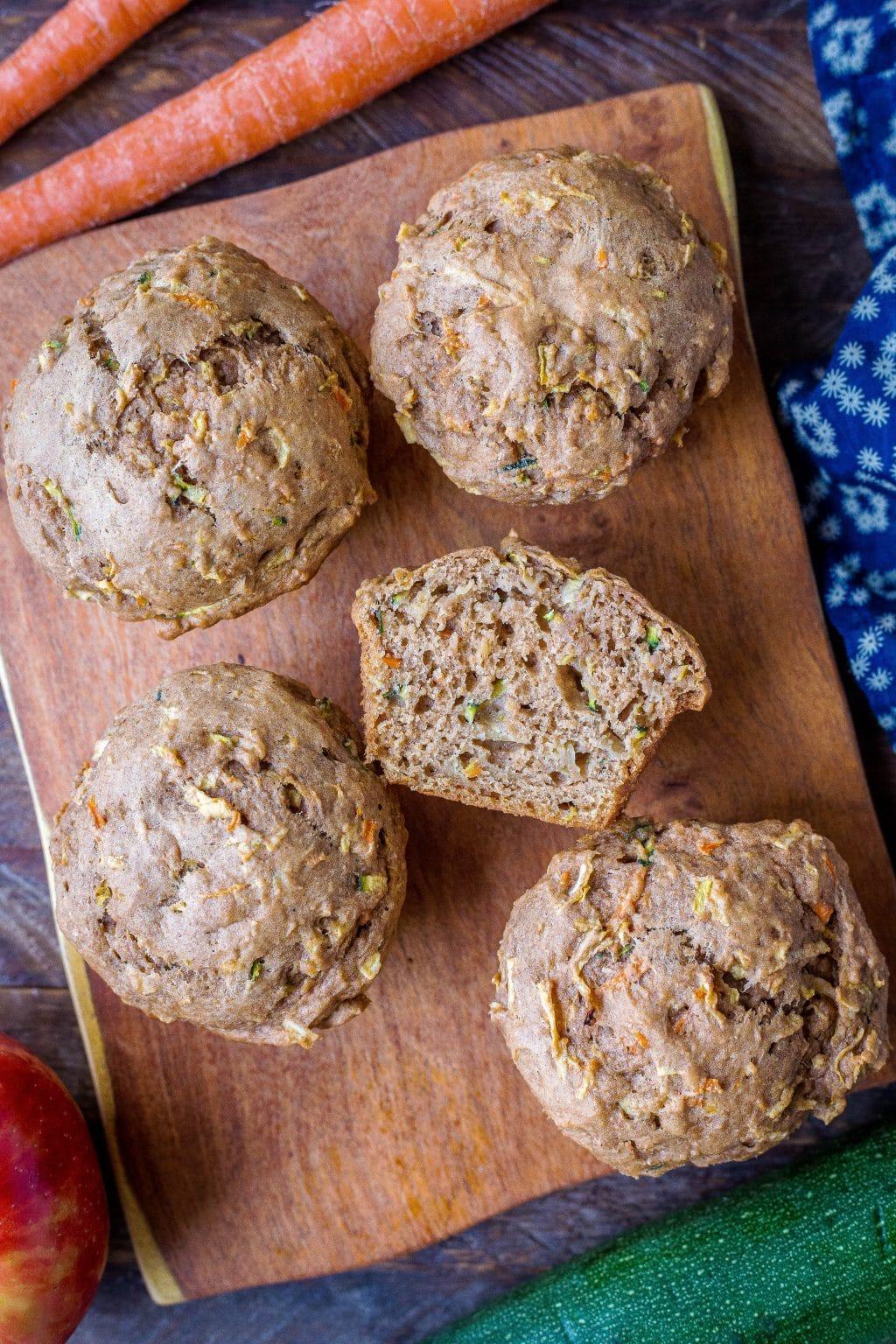 A few zucchini apple carrot muffins on a cutting board