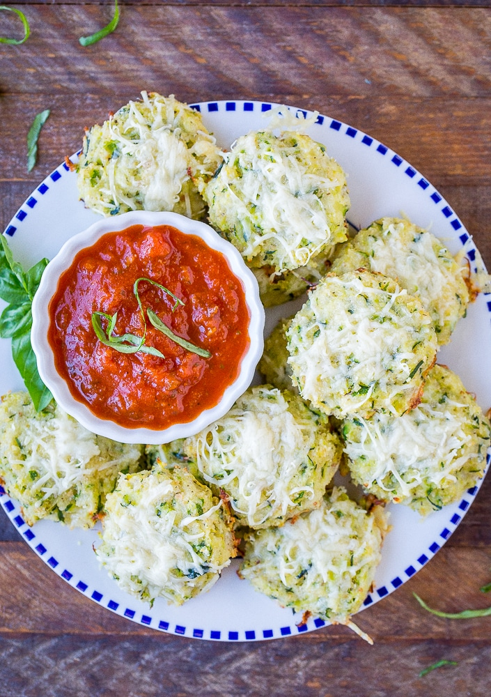A plate of Zucchini Pizza Bites with a bowl of marinara sauce