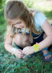 Girl picking flowers to add to her nature bracelet.