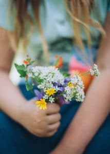 Girl holding a bouquet of wildflowers.