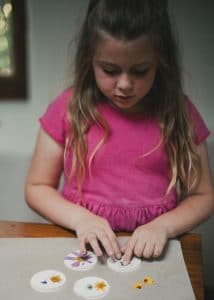 Girl decorating the clay ornaments with dried flowers.