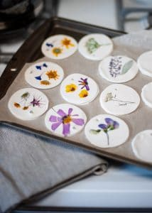 Several pressed flower clay ornaments on baking sheet.