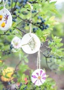 Flower pressed ornaments hanging from a tree.