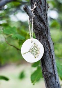 Flower pressed ornament hanging on tree.
