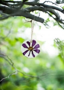 Flower pressed ornament hanging on a tree.