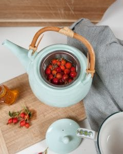 Brewing wild rose hip tea with fresh whole rose hips.