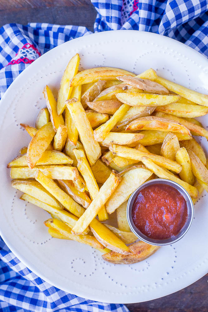 A bowl of homemade French fries with ketchup