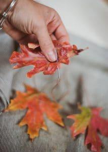Stringing wax leaves.