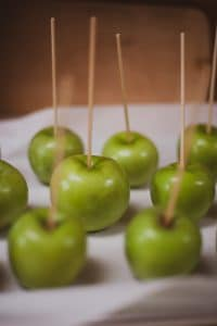 Green apples prepared for dipping in caramel.