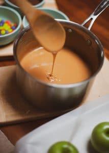 Caramel prepared for dipping Halloween caramel apples.