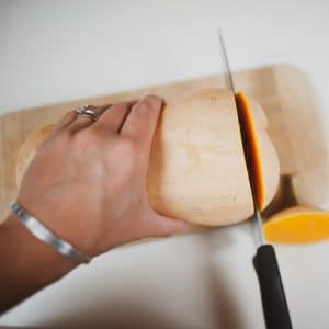 Cutting the ends off of a butternut squash.