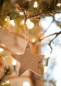 A finished lace star ornament hanging on a Christmas tree.