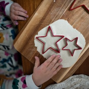 Child using a cookie cutter to cut out star shapes from lace pressed clay.