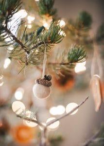 Felt acorn ornament hanging on Christmas tree.