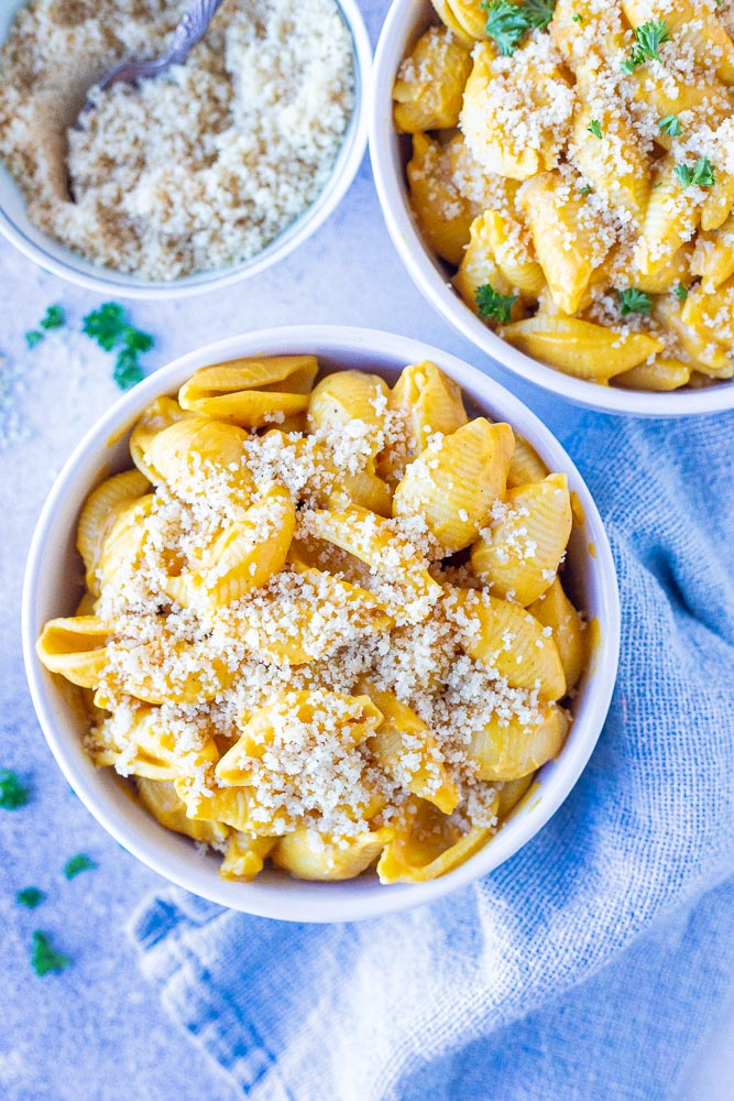 Two bowls of vegan butternut squash Mac and cheese with a bowl of breadcrumbs