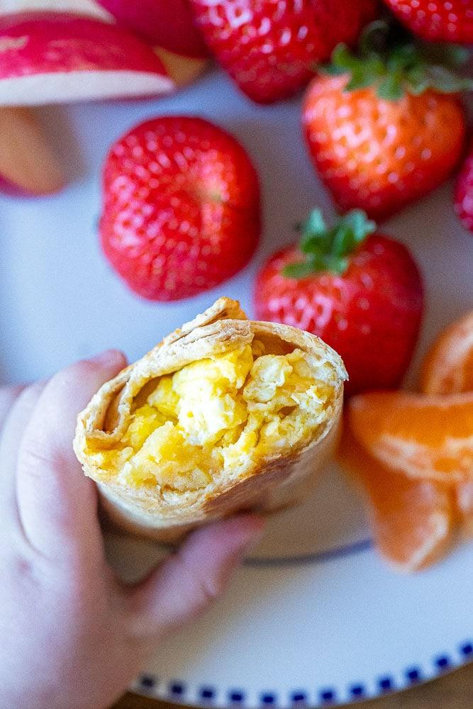 Little kid holding a breakfast burrito