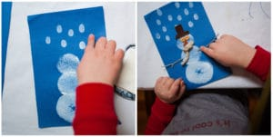 Child adding snowflakes and finishing touches to her snowman.