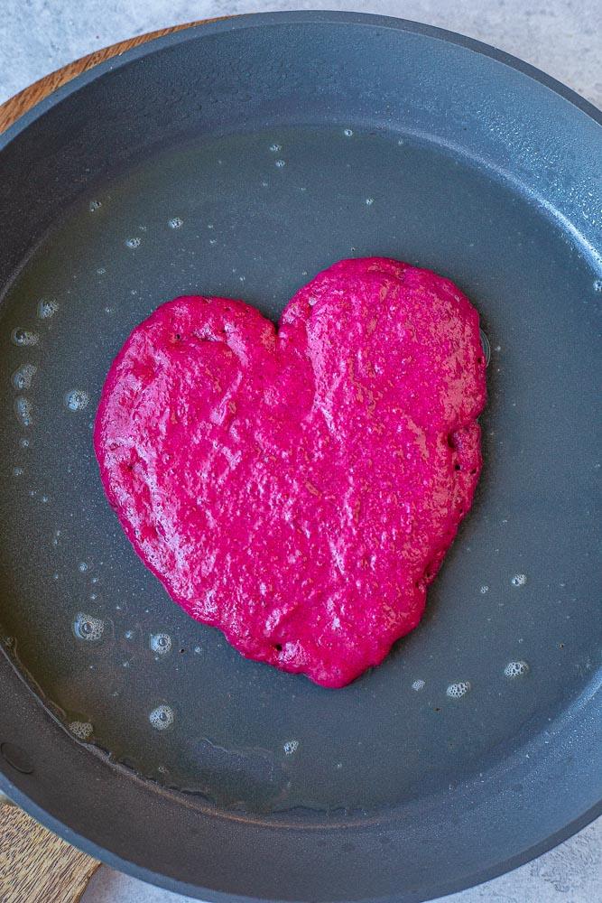 Pink heart pancake in a pan cooking