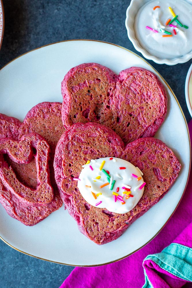 Plate of pink heart pancakes with whipped cream and sprinkles