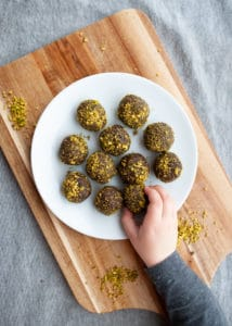 A plate of chocolate and pistachio energy balls.