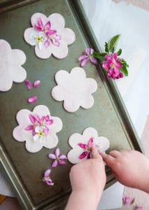 Child decorating flower clay cookies.