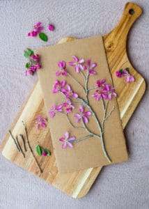Blossoms and twigs glued onto cardboard to make a tree.