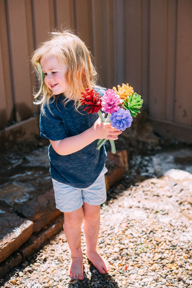 Child holding a bouquet of pinecone flowers