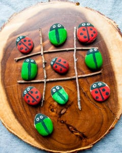 Tic-Tac-Toe game using twigs and rocks painted as bugs.