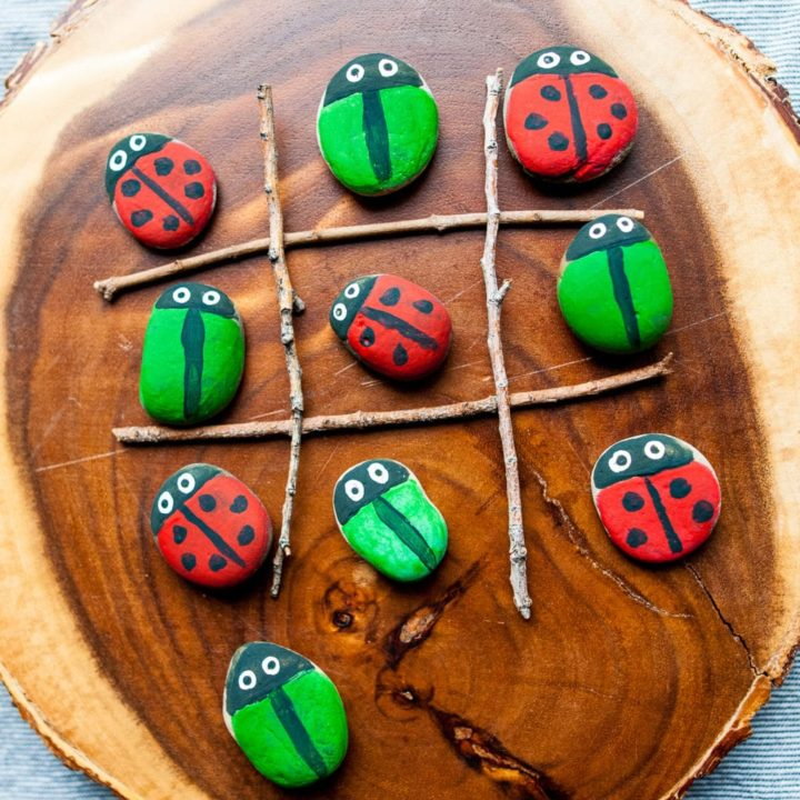 A game of tic-tac-toe using stone-painted bugs.