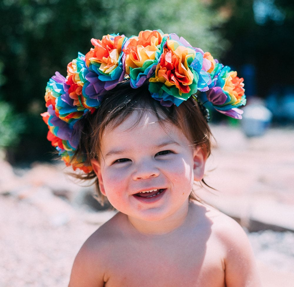 child wearing a rainbow flower crown
