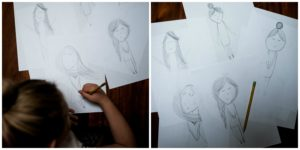 A child sketching out her characters for Nature Paper Dolls.