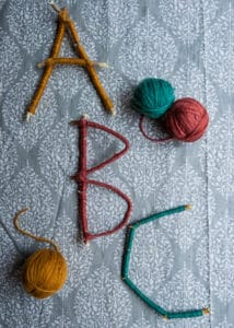 Letters made with twigs wrapped in yarn.