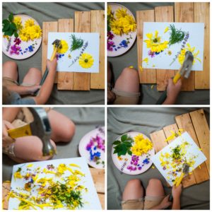 A child hammering flowers into a piece of paper to create flower stained stationary.