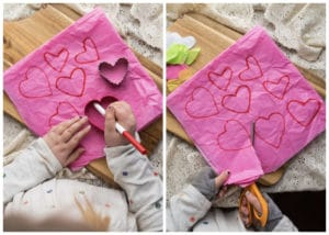 Child drawing and cutting out tissue paper hearts.