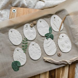 Nature items pressed into clay eggs for decoration.